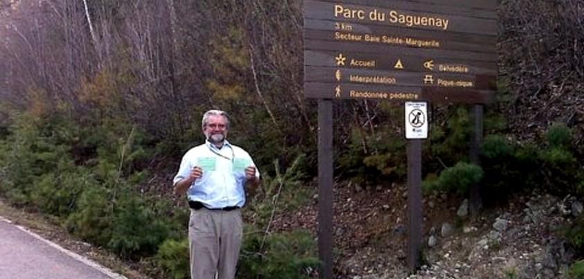Richard Bouchard sous un panneau indicateur du Parc du Saguenay