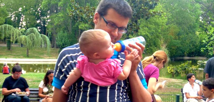 Un jeune père donne le biberon à son bébé dans un parc